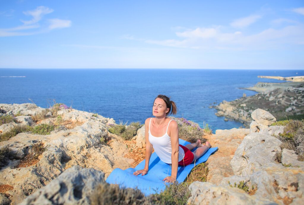 Woman In White Tank Top Doing Yoga Exercise On Rocky Shore 3779748 Min (1)